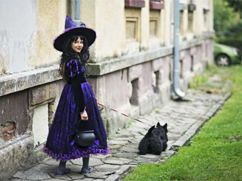 A woman dresses up as a witch walking her dog
